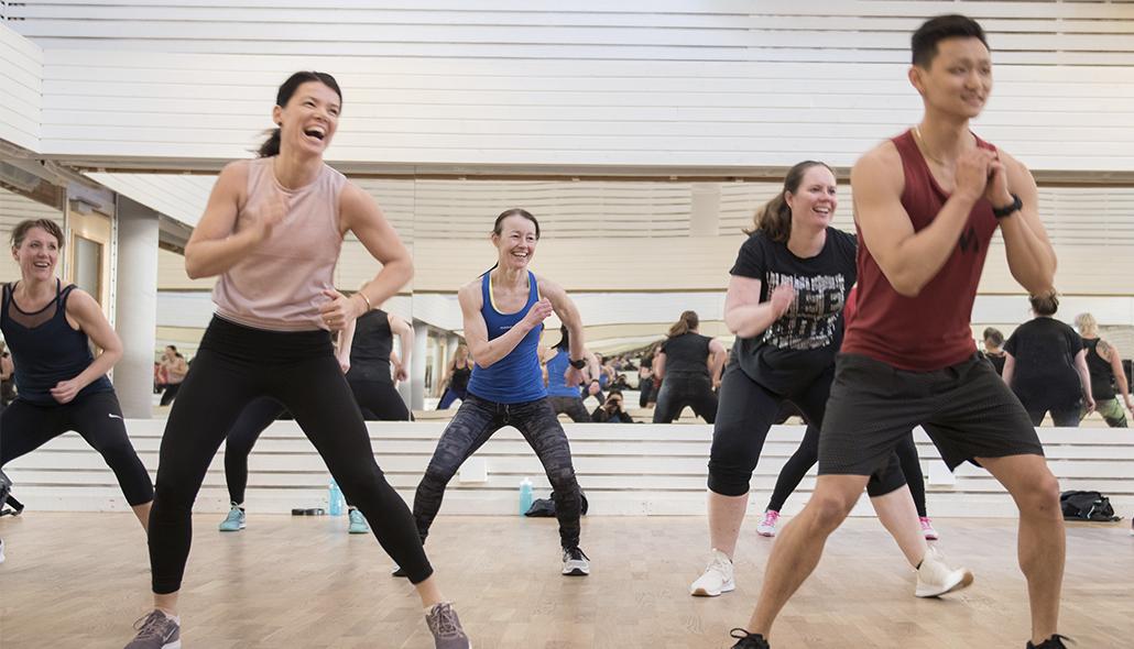 Ett gruppträningspass där deltagarna är mitt uppe i en rörelse och ser glada ut.